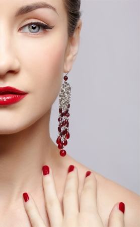 close-up portrait of young beautiful brunette woman in ear-rings touching her shoulder with manicured fingers photo