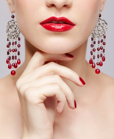 close-up portrait of young beautiful brunette woman in ear-rings touching her chin with manicured fingers