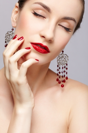 close-up portrait of young beautiful brunette woman in ear-rings touching her cheek with manicured fingers photo