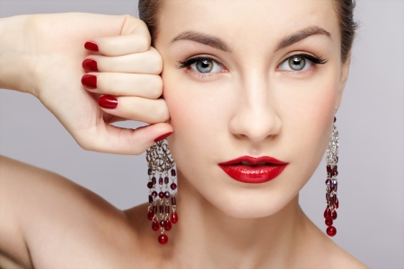 close-up portrait of young beautiful brunette woman in ear-rings touching her temple with manicured hand photo