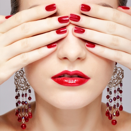 close-up portrait of young beautiful brunette woman in ear-rings closing her eyes with manicured hands photo
