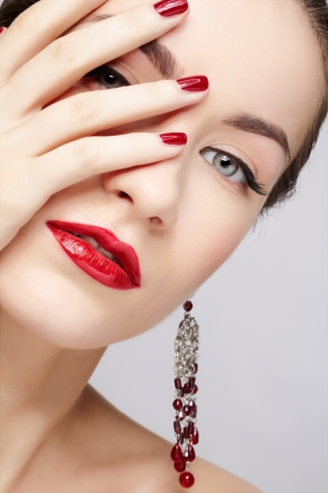 closeup portrait of young beautiful brunette woman in ear-rings closing half of her face with manicured hand photo