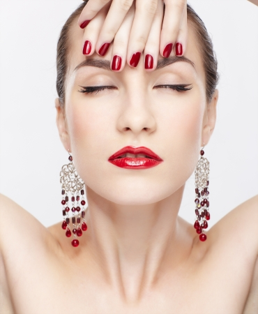portrait of young beautiful brunette woman in jewelry touching her forehead with manicured hand photo