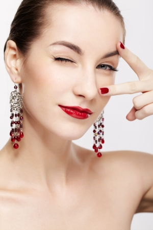 portrait of young beautiful brunette woman in jewelry winking photo