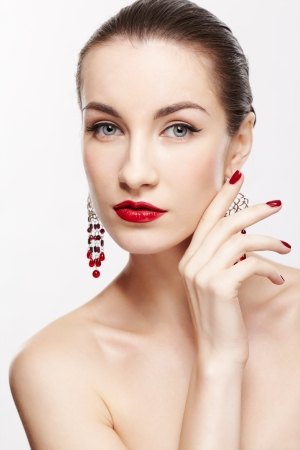 portrait of young beautiful brunette woman in jewelery with manicured fingers on gray photo