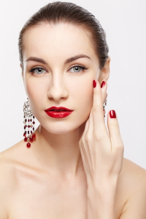portrait of young beautiful brunette woman in jewellery on gray touching her face with manicured hand photo