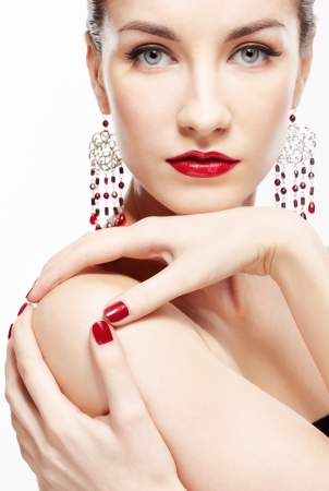 portrait of young beautiful brunette woman in ear-rings touching her shoulder with manicured fingers photo