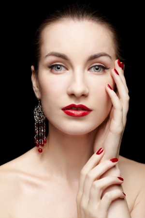 portrait of young beautiful brunette woman in jewellery on black touching her face with manicured fingers photo