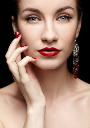 portrait of young beautiful brunette woman in jewelry on black touching her face with manicured hand photo