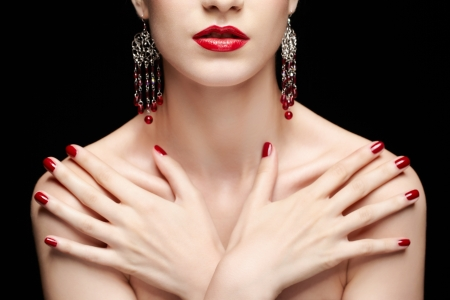 portrait of young beautiful brunette woman in jewelry with manicured hands on her chest Stock Photo