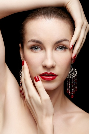 close-up portrait of young beautiful brunette woman in jewelry touching her head with manicured hands  photo