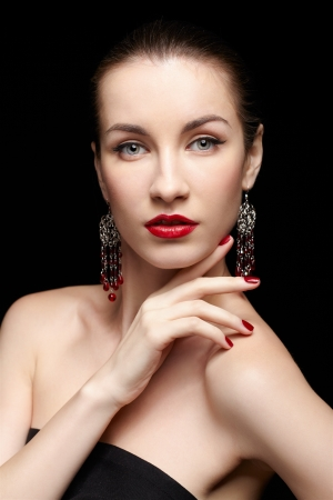portrait of young beautiful brunette woman in jewelery touching shoulder with manicured fingers photo