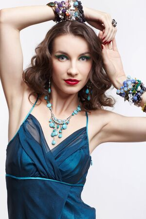 portrait of young beautiful brunette woman in blue dress and jewelery posing with hands over her head Stock Photo - 13701743