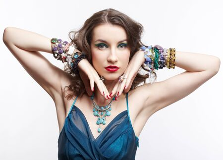 portrait of young beautiful brunette woman in blue dress and jewelry on gray photo
