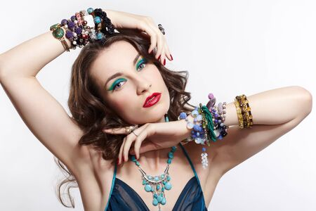 portrait of young beautiful brunette woman in blue dress in in rings, ear-rings, beads and bracelets Stock Photo - 13701670