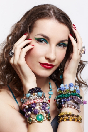 portrait of young beautiful brunette woman posing in blue dress, in beads, rings, ear-rings and bracelets on gray photo