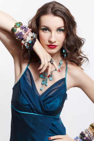 portrait of young beautiful brunette woman in blue dress, in beads, ear-rings, rings and bracelets Stock Photo - 13701671