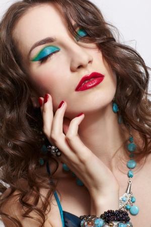 headshot portrait of young beautiful brunette woman in jewellery with eyes closed photo