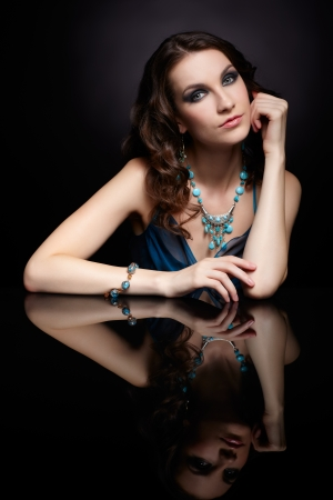 portrait of young beautiful brunette woman in jewelery sitting at black reflecting table