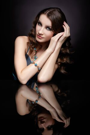 portrait of young beautiful brunette woman in jewellery sitting at reflecting table photo