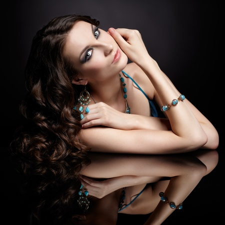 portrait of young beautiful brunette woman in jewellery at black mirror table Stock Photo - 13701496
