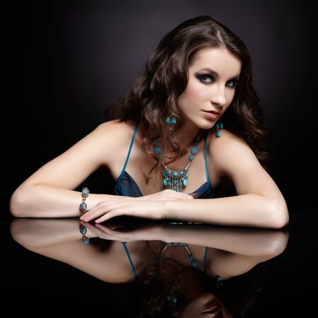 portrait of young beautiful brunette woman in jewelry at reflecting table Stock Photo - 13701491