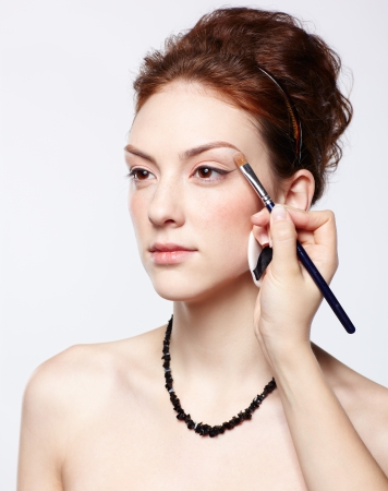 portrait of young beautiful woman maked up by makeup artist's hand putting on eyeshadow photo