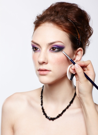 portrait of young beautiful woman maked up by makeup artist artists hand on violet eyeshadow photo