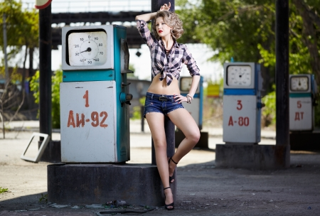 outdoor portrait of young beautiful blonde woman posing on gas station photo