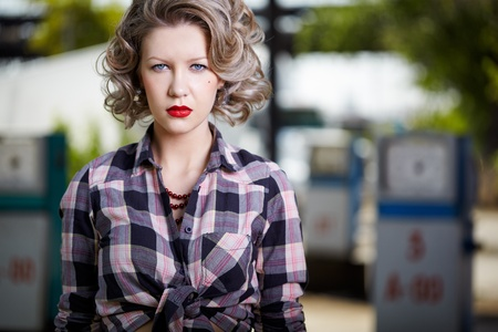 outdoor portrait of young beautiful blonde woman posing  on gas station with petrol pumps on background photo