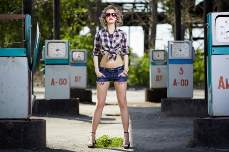 outdoor portrait of young beautiful blonde woman posing on gas station with a lot of petrol pumps around photo
