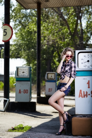 outdoor portrait of young beautiful blonde woman posing on gas station with a lot of gas pumps around photo