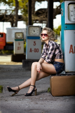 outdoor portrait of young beautiful blonde woman on gas station sitting on her travelling suitcase near gas pump photo