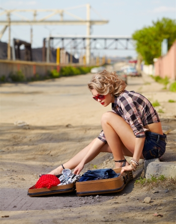 outdoor portrait of young beautiful blonde woman hitchhiker sitting on the roadside and opening her suitcase photo