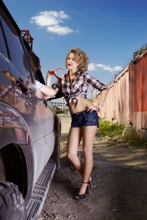 outdoor portrait of young beautiful blonde woman hitchhiker standing at side window and chating with driver photo