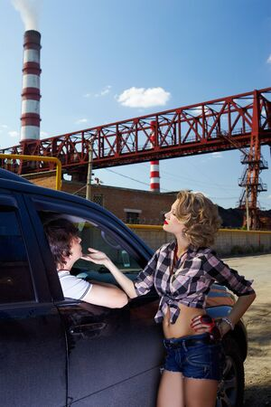 outdoor portrait of young beautiful blonde woman hitchhiker standing at side window and flirting with driver photo