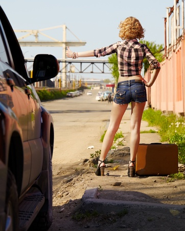 outdoor portrait of young beautiful blonde woman hitching the car on the roadside  photo