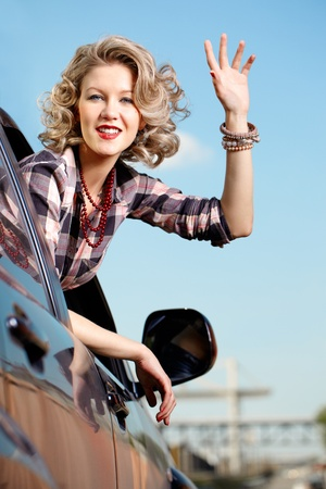 Blonde woman in car making goodbye wave  photo