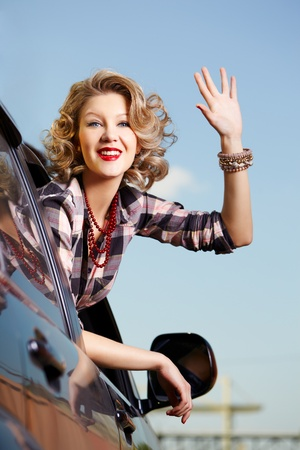 outdoor portrait of young beautiful smiling blonde woman looking bak through side window of car and waving hand photo