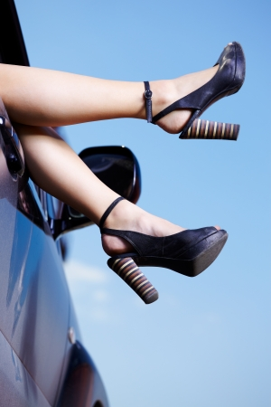outdoor shot of young beautiful woman's legs in court shoes in the side window of the car photo