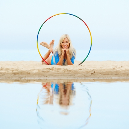 outdoor portrait of young beautiful blonde woman gymnast working out with hoop on the beach photo