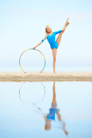outdoor portrait of young beautiful blonde woman gymnast training with hoop on the beach photo