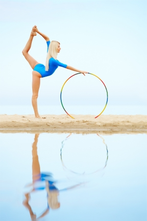 outdoor portrait of young beautiful blonde woman gymnast training with hoop on the sand photo