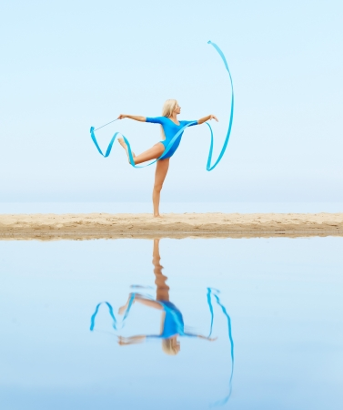 outdoor portrait of young beautiful blonde woman gymnast training with ribbon on the beach photo
