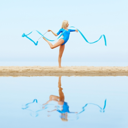 outdoor portrait of young beautiful blonde woman gymnast working out with ribbon on the beach photo