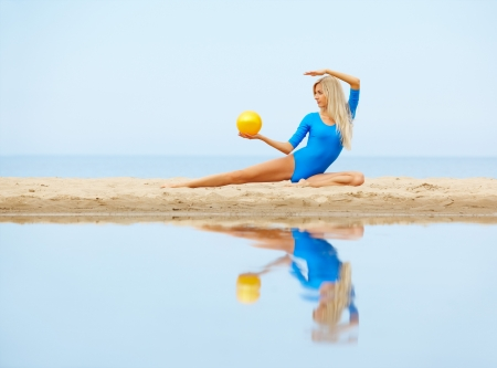 outdoor portrait of young beautiful blonde woman gymnast working out with ball on the beach photo