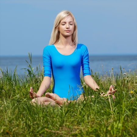 outdoor portrait of young beautiful blonde woman gymnast meditating in yoga lotus pose on grass photo