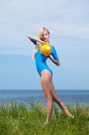 outdoor portrait of young beautiful blonde woman gymnast working out with ball on grass photo