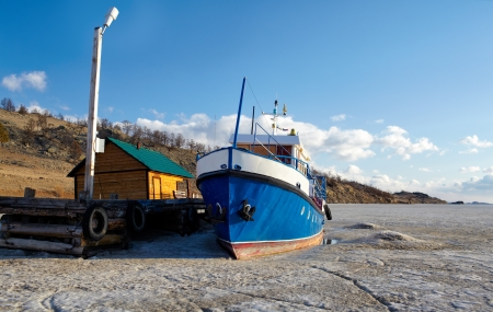 winter view of boat at moorage in frozen baikal lake photo