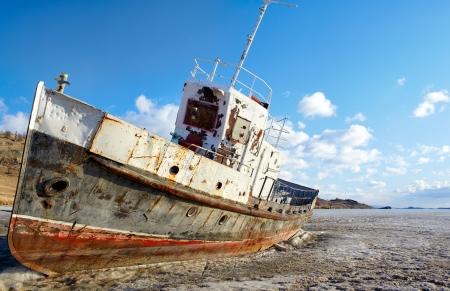 winter view of old rusty abandoned ship at frozen baikal lake photo